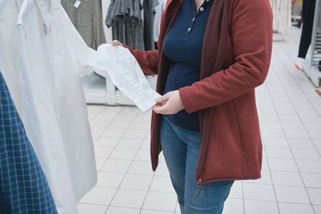 Pregnant woman in the store chooses a new white business shirt for her husband. Concept of buying new clothes, fashion, beauty. Hands close up shot