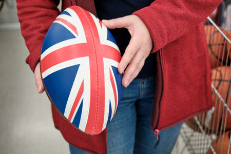 Woman in a shop buys a rugby and American football ball with a print of the British flag. Concept of strength sports, women independence and gender equality. Hands close up shot