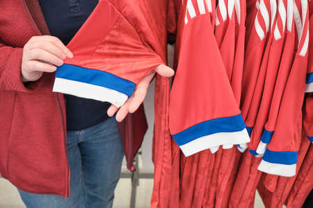 Woman in a store chooses a T-shirt for sports with a print of the flag of the Russian Federation. The concept of an active lifestyle and national paraphernalia. Hands close up shot