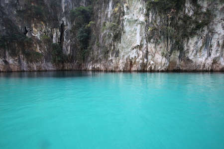 clean green water infront of the cliff in Rajjaprabha dam, Surat Thani province, Thailand Stock Photo