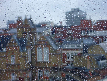 Raindrops decorate a window on a foggy rainy London afternoon.