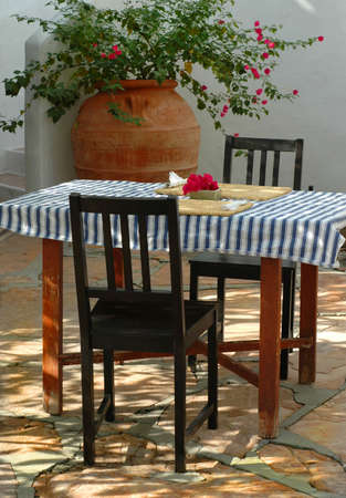 An inviting greek style courtyard breakfast table with tablecloth.