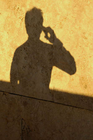 Shadow of a man talking on the phone