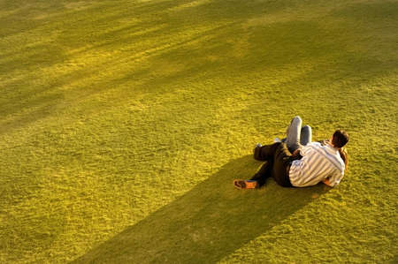 Couple on grass relaxing as the sun sets. Archivio Fotografico