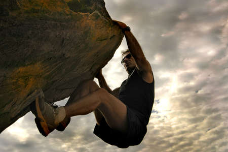 bouldering: Rock climber reaching for the sky.