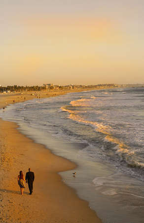 A couple stroll along a California beach at Sunset