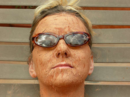 Woman wears her sunglasses while getting a mud facial
