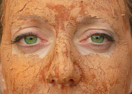 Close up of green-eyed woman with mud facial