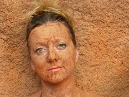 caked: Woman with facial mud blends into background