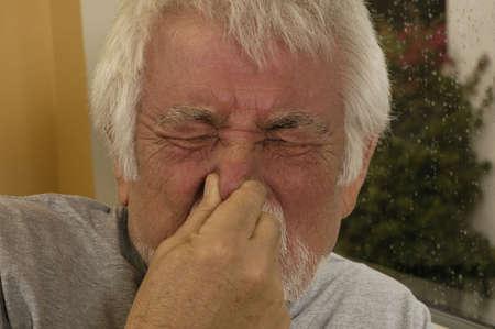Older man holding nose sneezing. Imagens