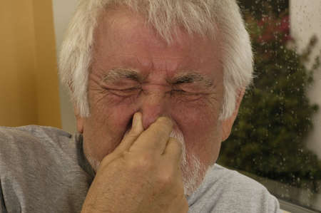 congested: Older man holding nose sneezing. Stock Photo