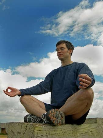 Man meditates outside on a bench Stock fotó