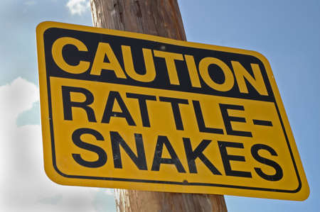 cautionary: Caution Rattle-Snake sign hanging on post