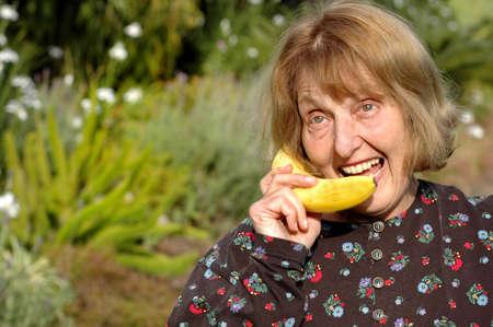 Older woman talks into banana instead of phone photo