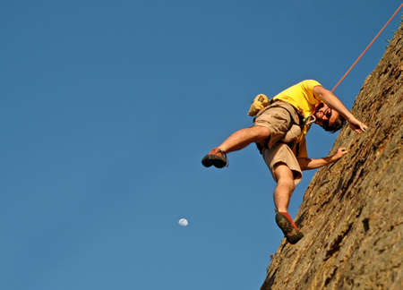 handhold: A rock climber baleys off cliff as moon rises