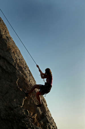 rappel: A woman climbs a cliff in California