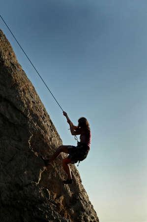 belay: A woman climbs a cliff in California