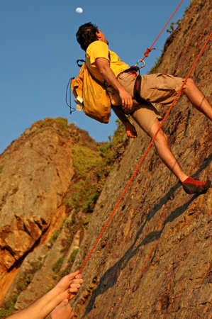 belaying: Climbers belaying off a cliff at sunset with moon rising