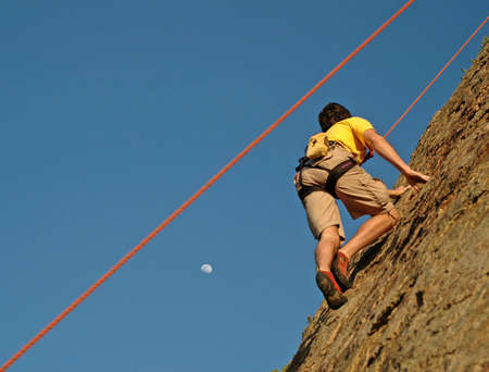strive: Climber climbs up California Cliff at Sunset and moon rise