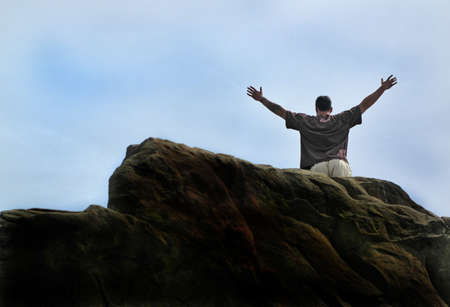 grasp: Man successfully climbs huge rock face Stock Photo