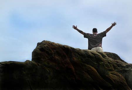 Man successfully climbs huge rock face Imagens