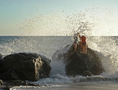 Couple braves the crashing waves at a California beach photo