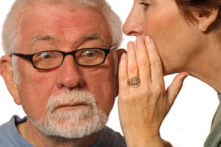 conspire: Wife whispers into husband ear Stock Photo