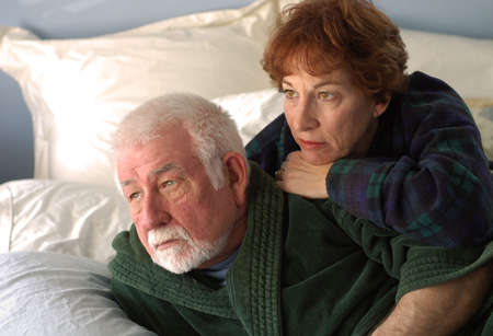 somber: An older couple snuggle together in the early morning. Stock Photo