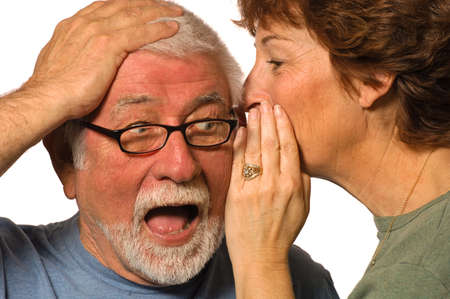 conspire: Wife whispers into husbands ear, surprising him Stock Photo
