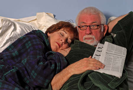 Couple in bed sleeps and reads