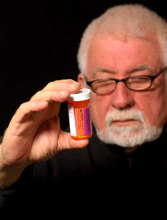 medicate: Man hold pill bottle and reads label.