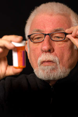 unclear: Older man tries to read pill bottle