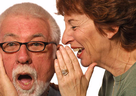 conspire: Woman laughs and whispers into husbands ear