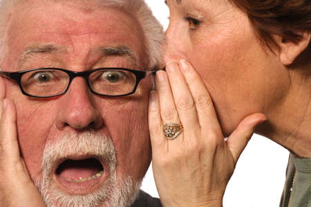 proposition: Woman whispers a scary secret into husbands ear Stock Photo