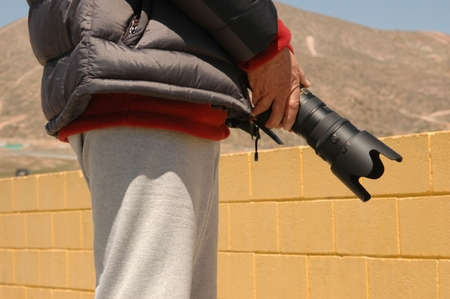 Man stands holding his BIG camera lens