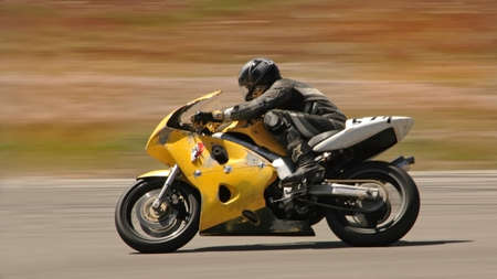 Motorcycle rider on yellow bike speeds by