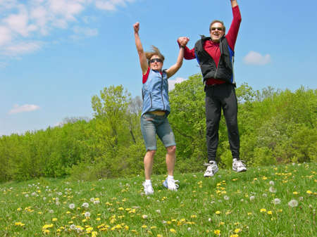 A couple jumps for joy in a meadow Archivio Fotografico