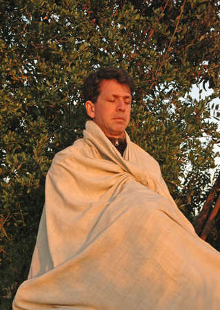 Man meditates peacefully at sunset
