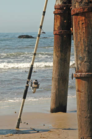 A fishermans pole leans on a pier Imagens