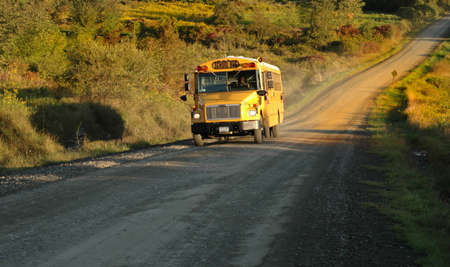employment elementary school: A country school bus makes its way along its route Stock Photo