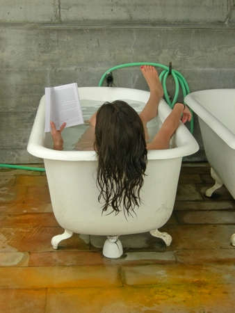 soaks: A woman soaks in a tub while reading.