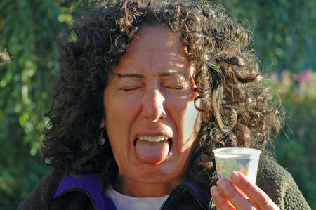 Woman tastes aweful medicine Stock fotó