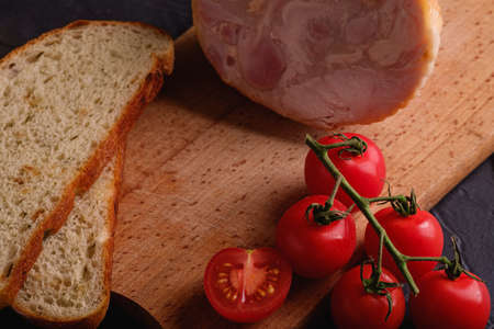 Turkey ham meat, fresh cherry tomatoes branch and loaf sliced bread on wooden cutting board, black textured background, angle view macro Reklamní fotografie