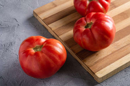 Three pink heirloom tomato vegetables, fresh red ripe tomatoes on wooden cutting board, vegan food, stone concrete background, angle view