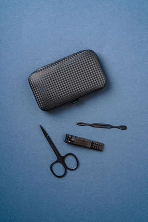 Set of manicure and pedicure tools and accessories near to case, top view, blue background
