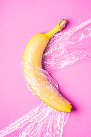 Banana fruit wrapped in stretch wrap plastic on pink background, minimalistic creative layout, ecology and environment concept