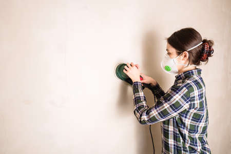 Woman in protective mask working with electric sander to smooth plaster wall surface, room renovation concept