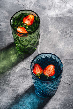 Two green and blue geometric glass cup with fresh water and strawberry fruits with colorful shadow light rays on stone concrete background, angle view