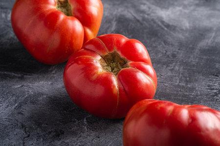 Three pink heirloom tomato vegetables in row, fresh red ripe tomatoes, vegan food, dark stone concrete background, angle view macro
