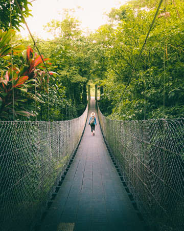 Woman walking on the bridge in the jungle of Costa Rica.